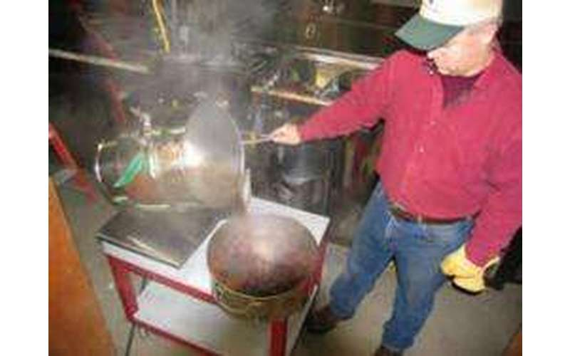 a man pouring hot maple sap