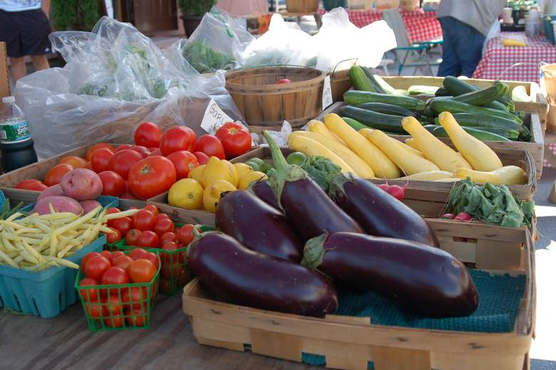 eggplant, squash, and more vegetables at a market stand