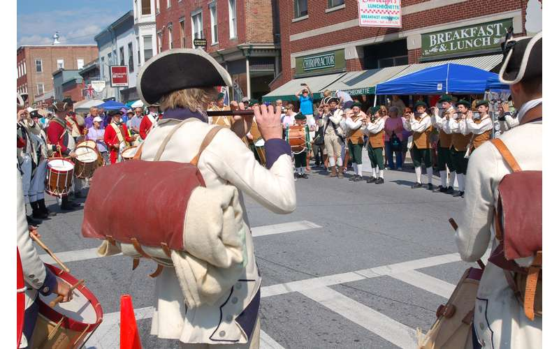 fife and drum players performing for a crowd on a street