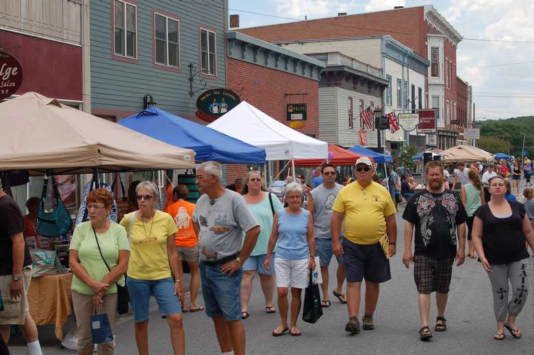 people walking down Montcalm Street by vendor tents for Ticonderoga's Streetfest