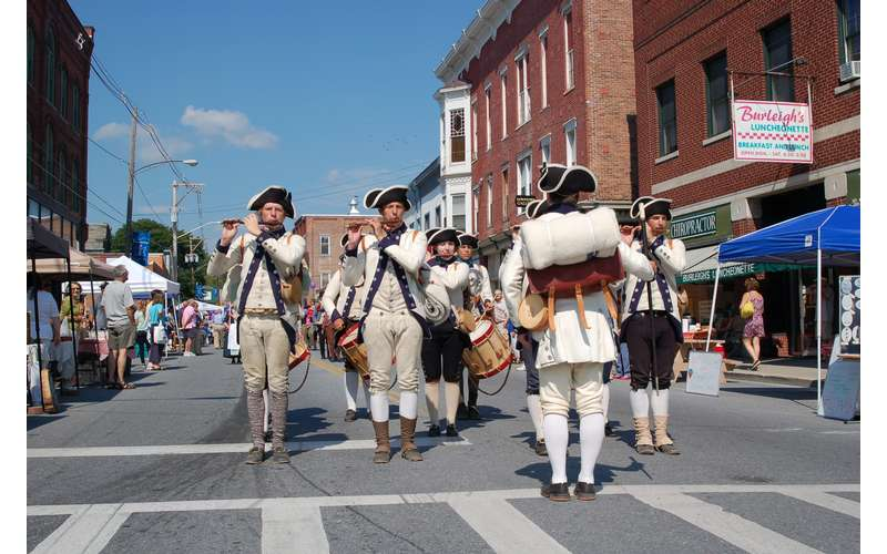 fife and drum corps standing on a street playing instruments