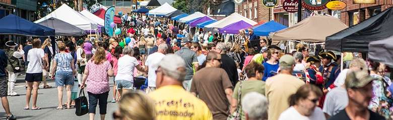 crowds browsing vendor tents on montcalm street in ticonderoga