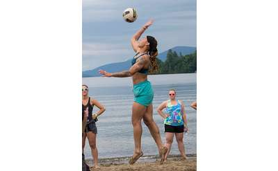 woman hitting volleyball on beach