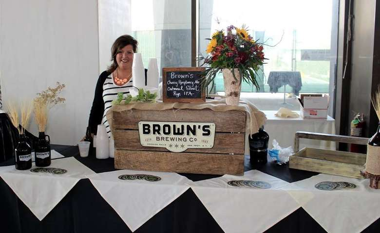 a woman standing behind a brewery table