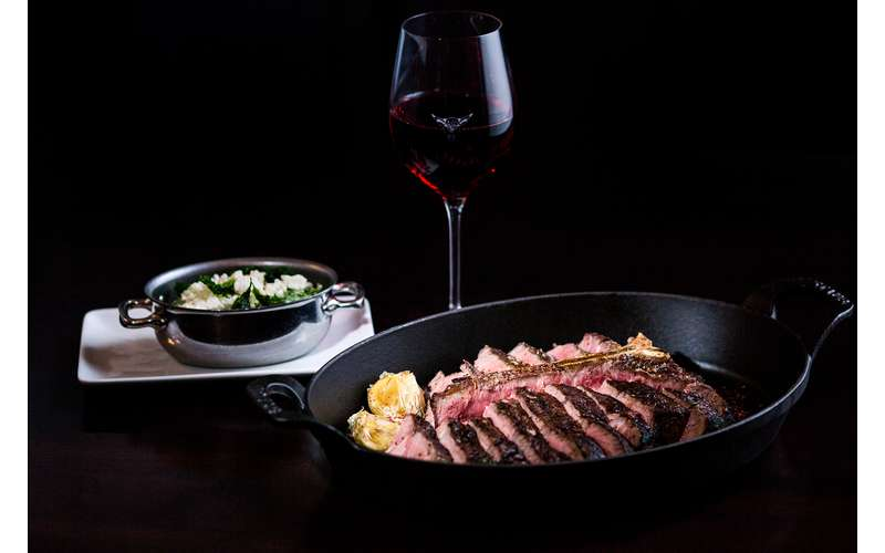 glass of wine with meat entree
