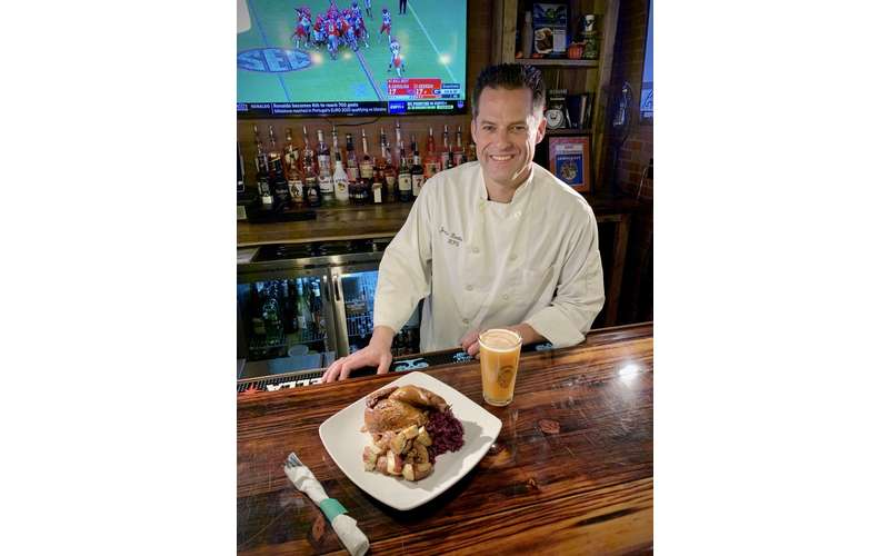 bartender with beer glass and plate of food on the bar