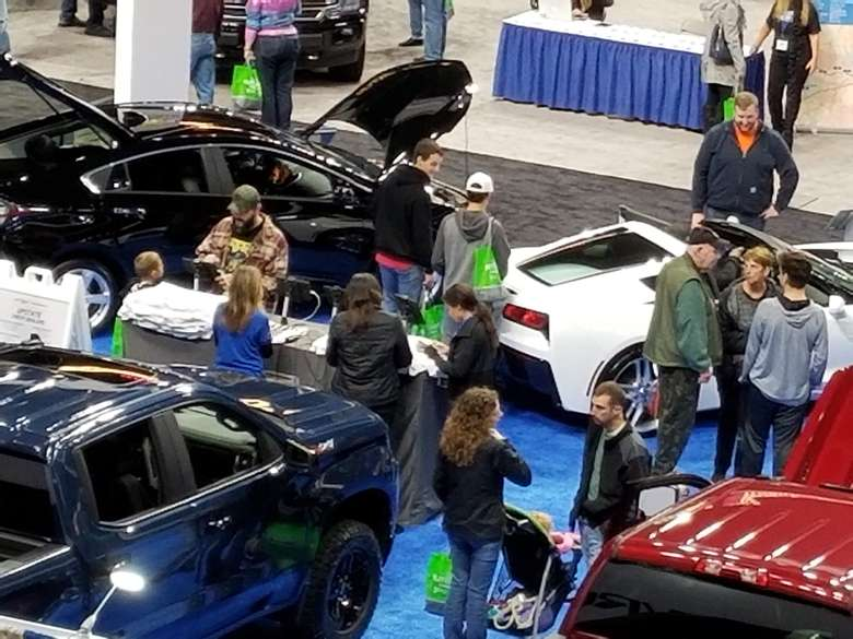 car checking out cars at a show
