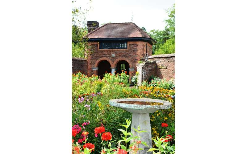 a brick structure on the outskirts of a garden with a fountain near the flowers