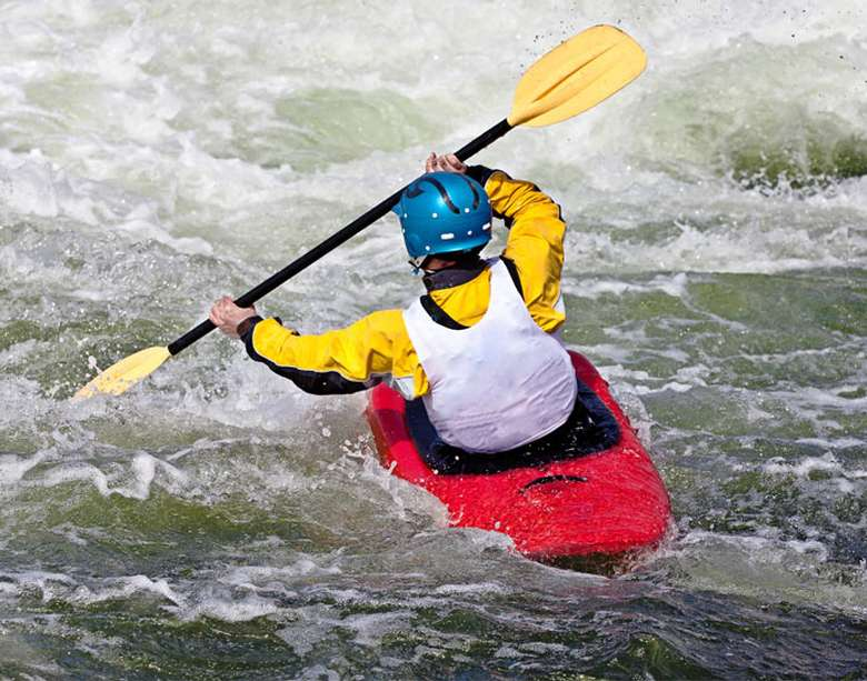 kayaker paddling through rapids
