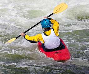 kayaker paddling through rapids