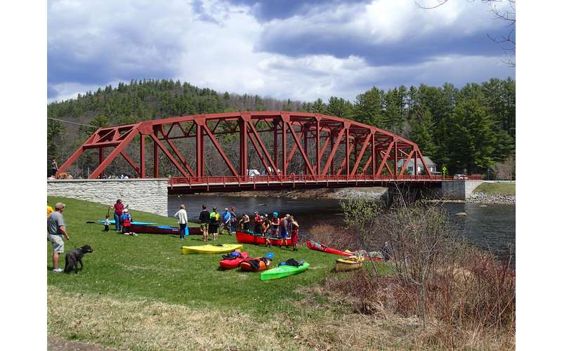 bridge with canoes and kayaks in front of it