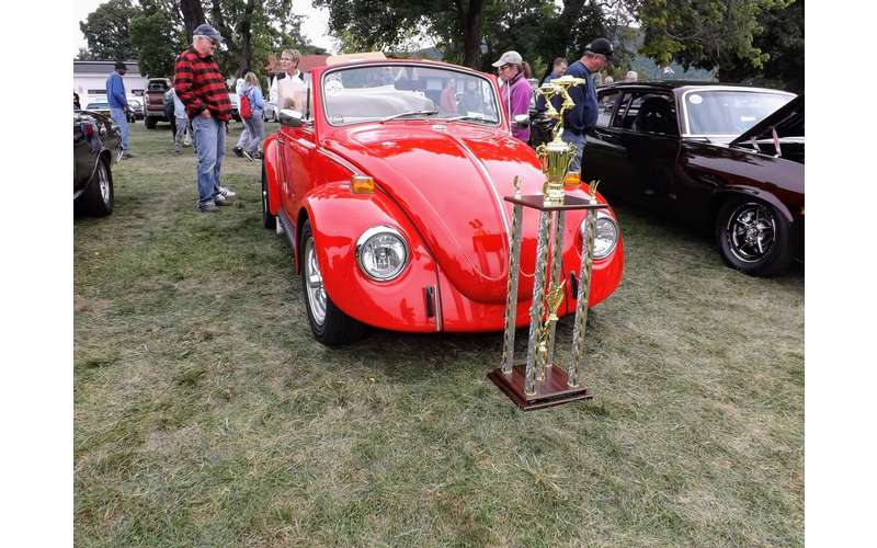 red bug car with trophy in front of it