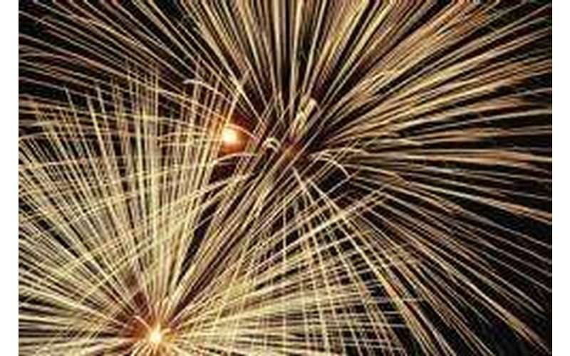 close up of large yellow fireworks in a pitch black sky