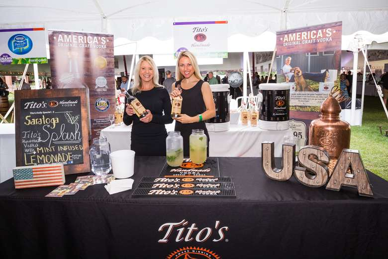 women holding titos vodka