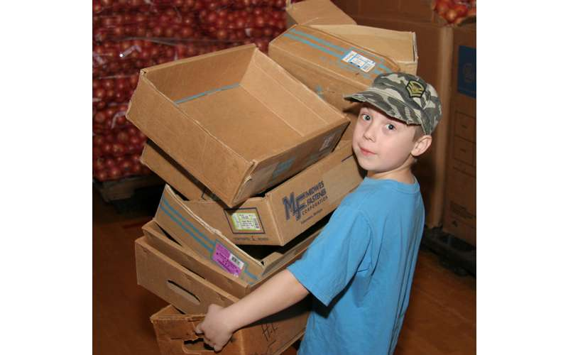 little boy with camo hat carrying a bunch of boxes