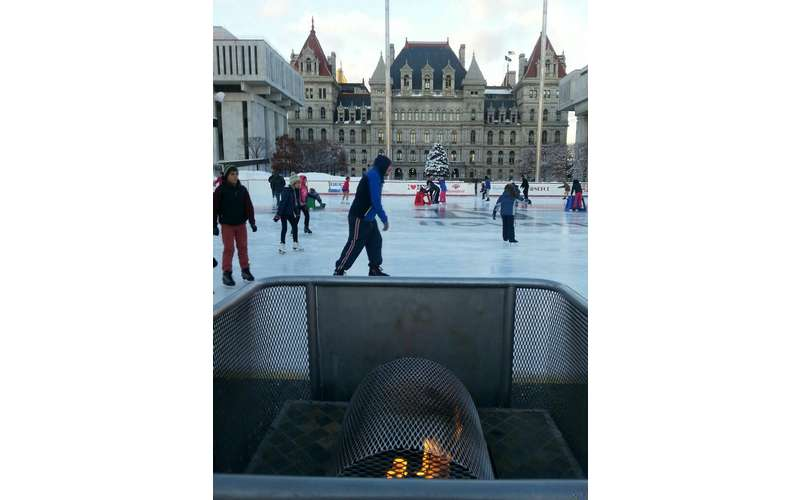 people skating in front of the plaza with some sort of fire in the foreground