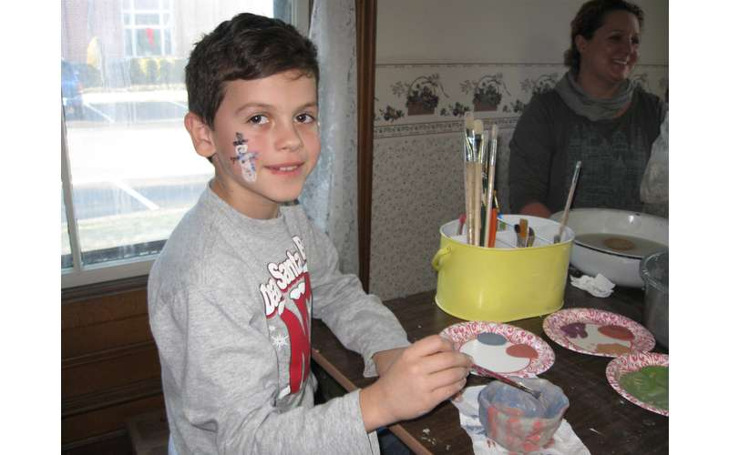 boy with holiday face paint and crafts
