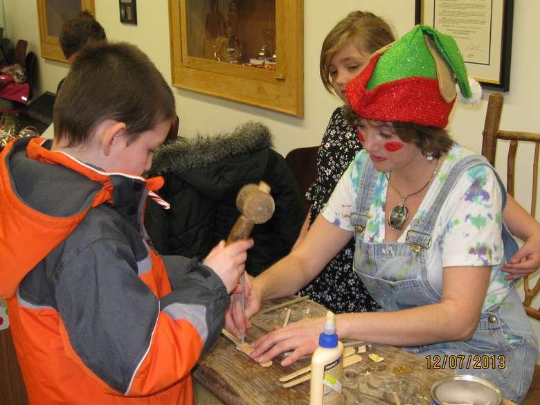 a woman dressed like an elf helping a boy