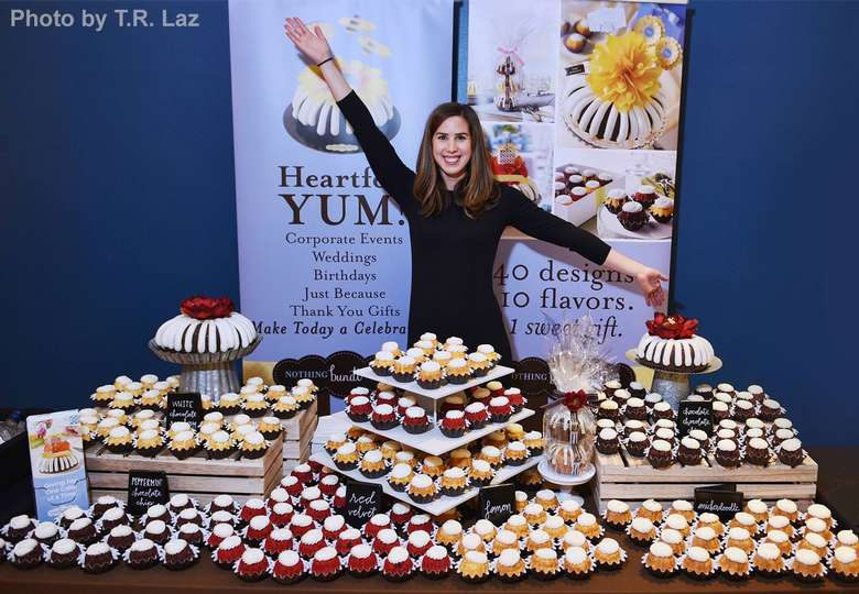 woman standing behind a display of cupcakes