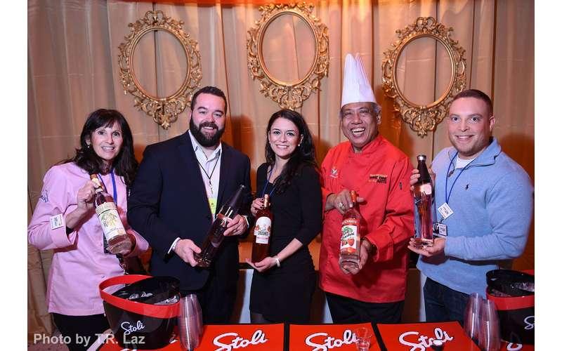 five people holding bottles of vodka