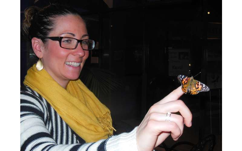 a woman with a monarch butterfly on her finger