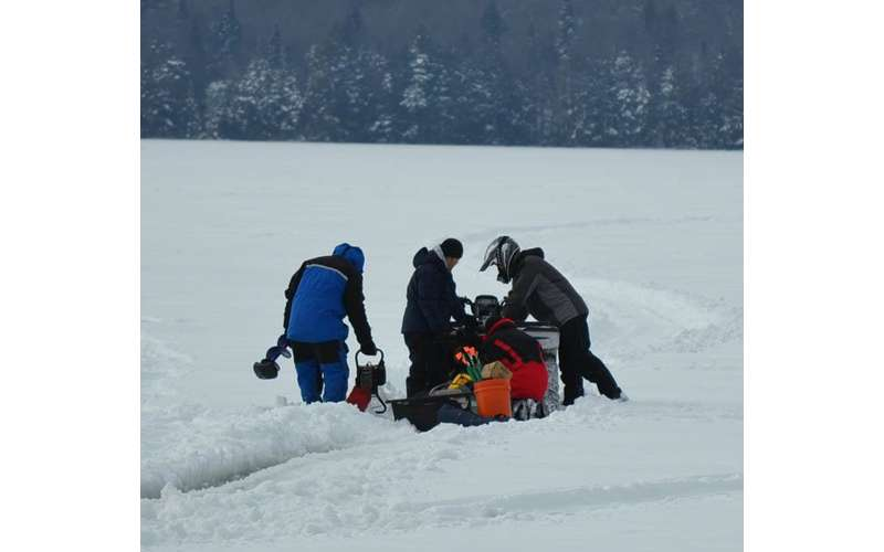 group of people moving ice fishing gear