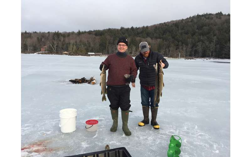 two people standing on ice with their ice fishing catches of the day