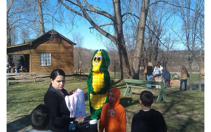 group of people outside with a person in a corn cob costume