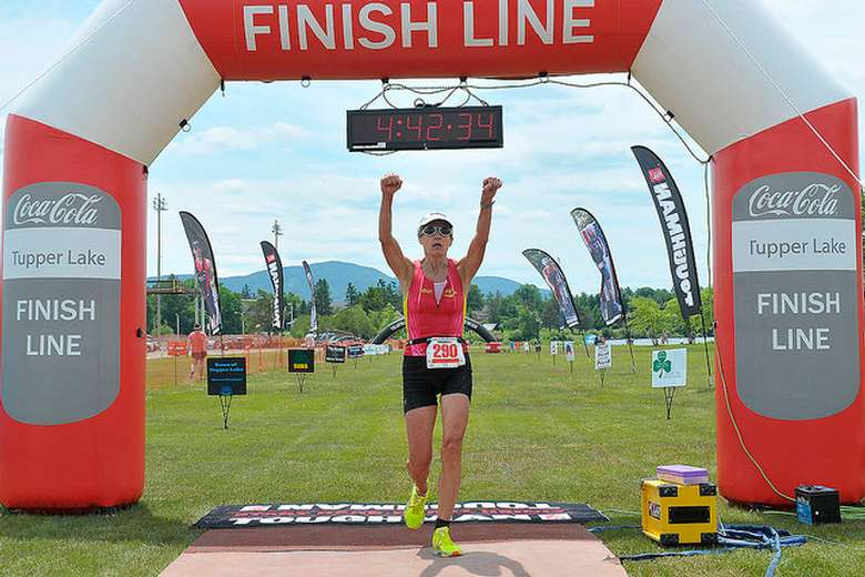 woman holding up arms crossing finish line