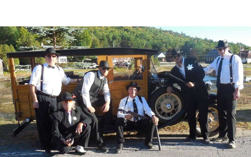 group of reenactors near old vehicle