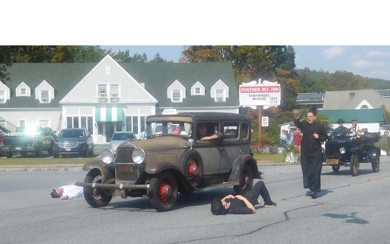 old vehicles and reenactors in road