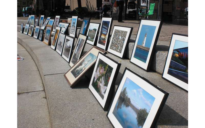 lineup of framed pictures along the street