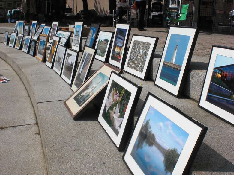 a lineup of framed pictures in the street
