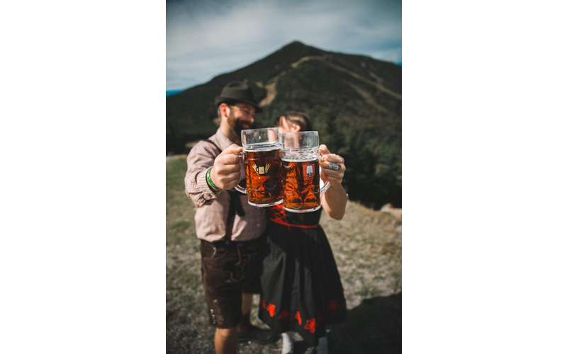 couple holds up beer by mountain
