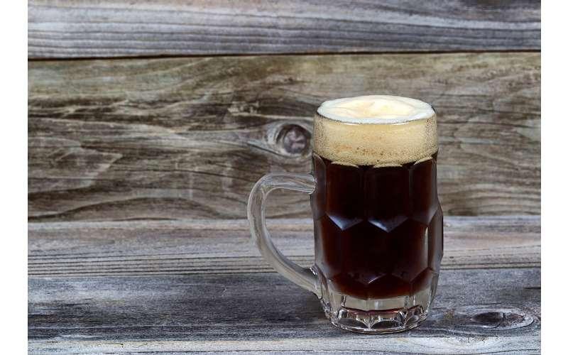 a dark beer in a glass mug