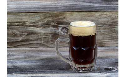 a dark beer in a glass mug