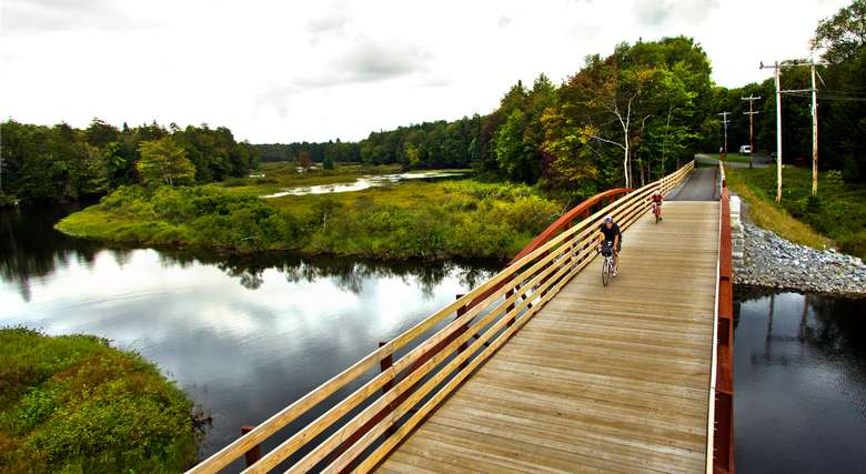 bikers riding across a wooden bridge with scenic views