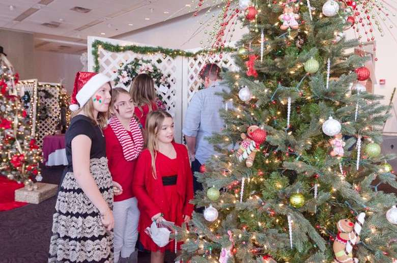 three people looking at decorated holiday tree