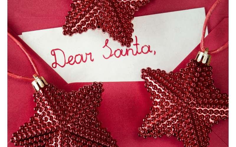a letter to Santa tucked into a red envelope with red ornamental stars surrounding it