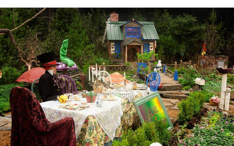 an alice in wonderland-themed garden display with a long table