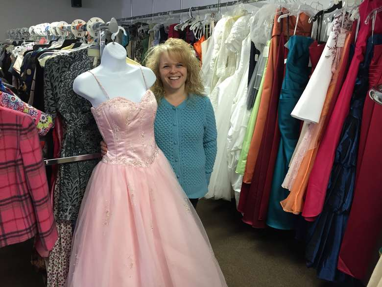 a woman holding up a prom dress in a store