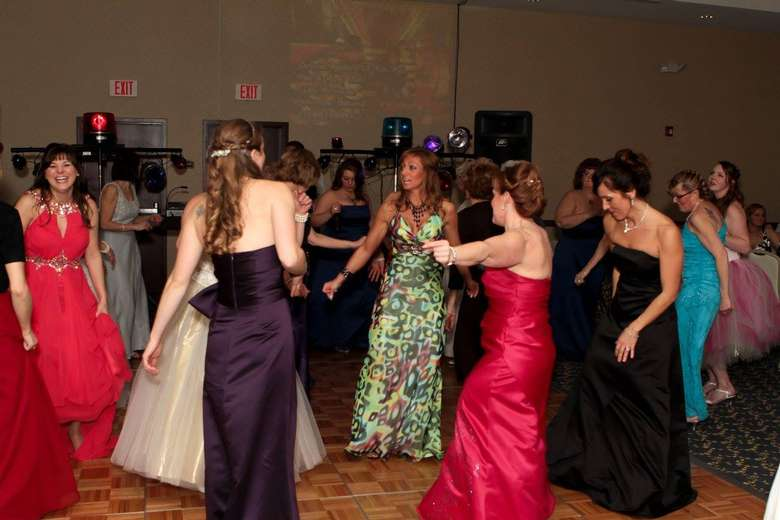 women in prom dresses on a dance floor