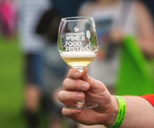 person pouring wine into a sample glass with text about the festival dates and tickets