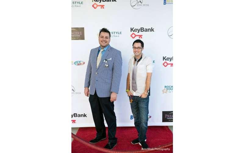 two men posing on a faux red carpet