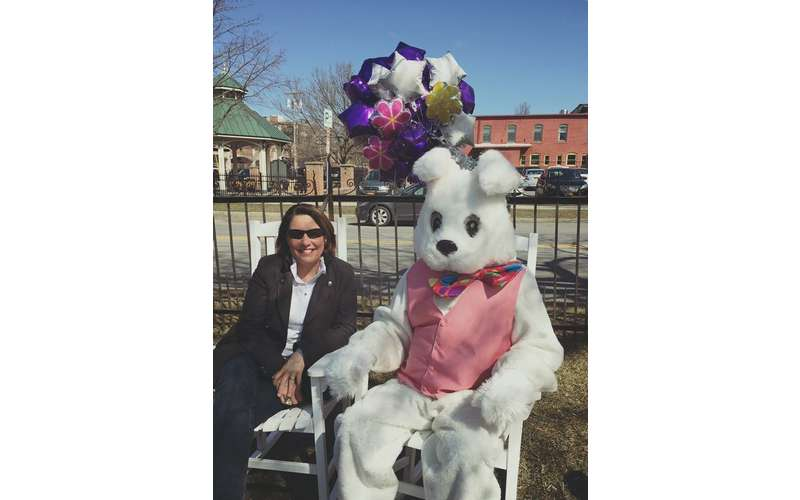 a woman sitting next to the easter bunny outdoors