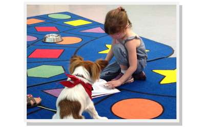 Young girl reading to a therapy dog