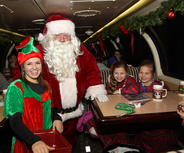 santa, an elf, and two girls on a train