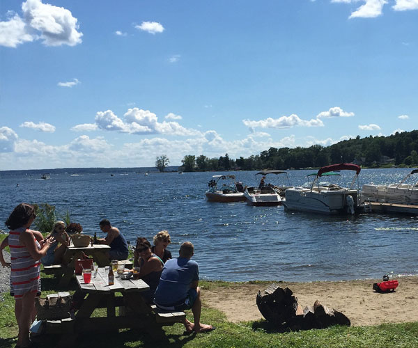 people sitting at a picnic table on saratoga lake with boats docked in the background