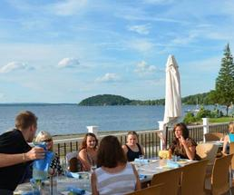 people dining on patio near the water