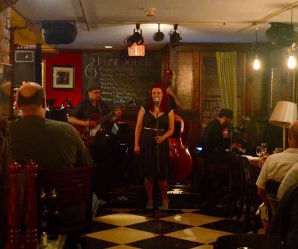 a woman performing at a jazz bar with a band behind her